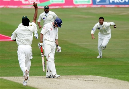 Andrew Strauss looks down as Younis Khan celebrates his catch