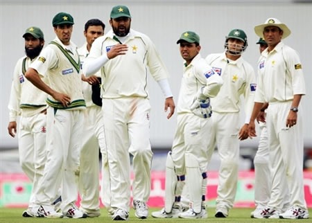 Pakistan team looks concerned as the umpires inspect the ball they think has been tampered
