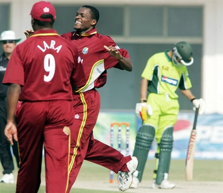 Powell celebrates the wicket of Imran Farhat with Lara