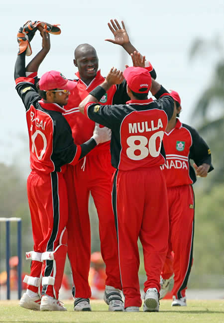 Henry Osinde celebrates the wicket of Shoaib Malik with his teammates