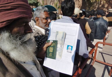 An elderly fan holds his passport and visa application