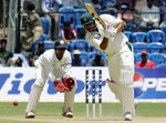 Inzamam-ul-Haq drives as wicketkeeper Dinesh Karthik looks on
