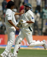 Inzamam-Ul-Haq takes a run as Irfan Pathan gestures