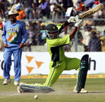 Shoaib Malik is watched by Virender Sehwag