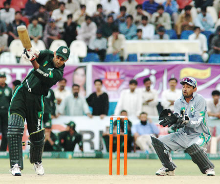 Zeeshan Khan drives as Khalid Mahmood looks on