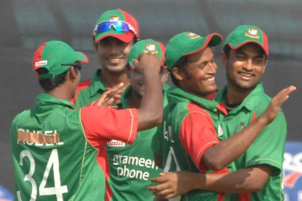 Nazmul Hossain is mobbed by mates after he had taken a spectacular  diving catch at point to get rid of Malcolm Waller