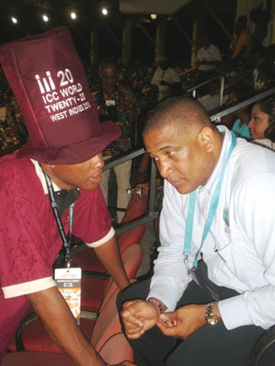 Dr. Ernest Hilaire (right) listens to Super Fan, Peter Matthews