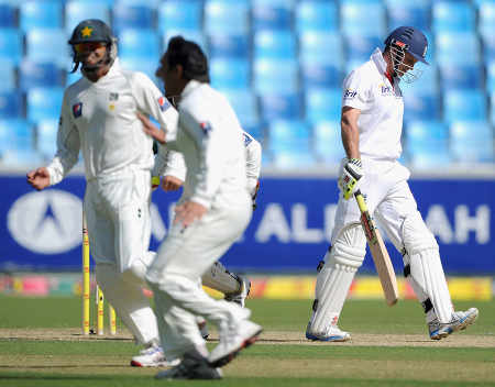 Saeed Ajmal is jubilant as Andrew Strauss walks back after being bowled,