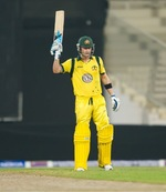 Michael Clarke raises his bat after completing his fifty