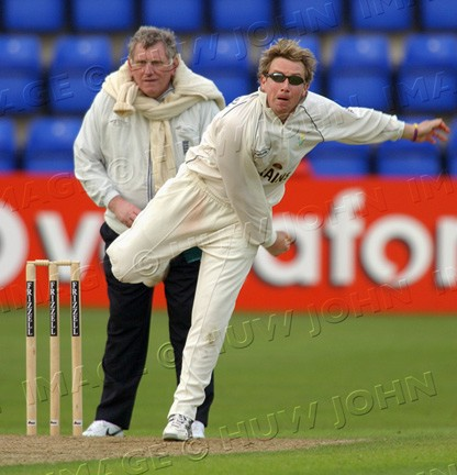 Robert Croft in bowling action against Surrey at Sophia Gardens, watched by umpire Graham Burgess