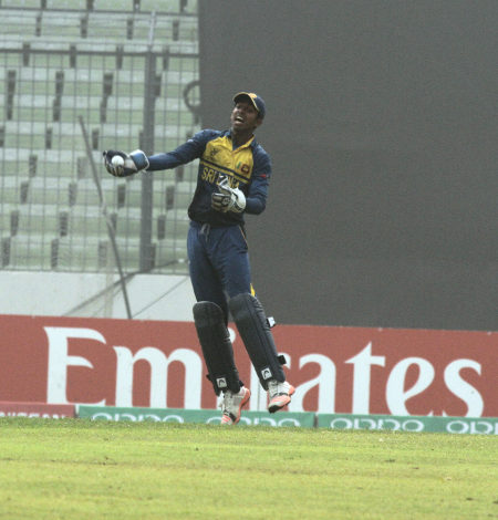 The Sri Lankan keeper celebrates after taking a catch