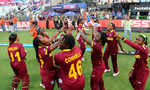 World Cup winning West Indies side point towards the sky while celebrating