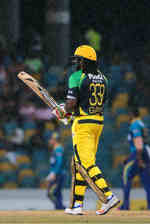 Chris Gayle walks back after rain stopped play