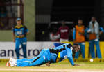The bowler dives to stop the ball