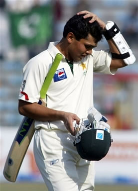 Kamran Akmal walks back to the pavilion